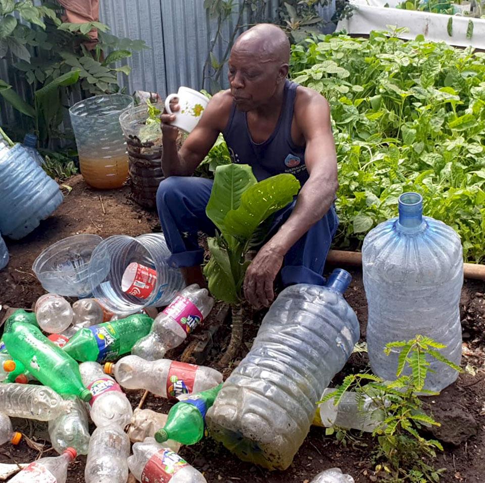 Joshua-among-plastic-bottles-Growht4Change